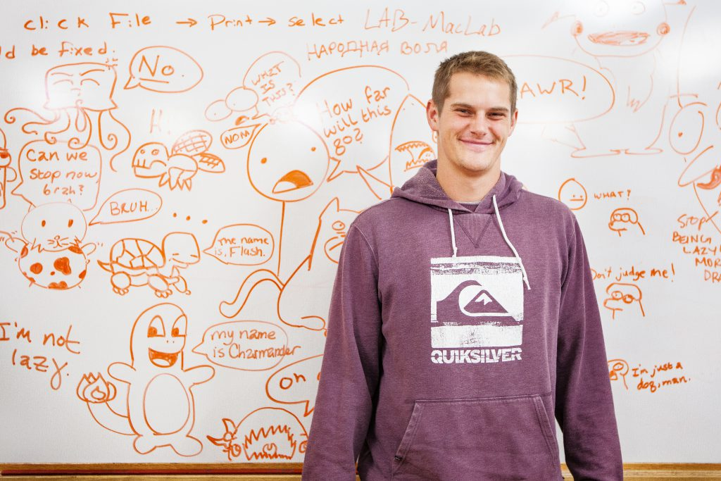 Illustration Major Student standing in front of doodles on whiteboard