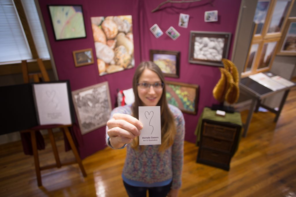 Student with her senior art display