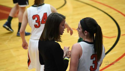 Women's Basketball coach instructing a player