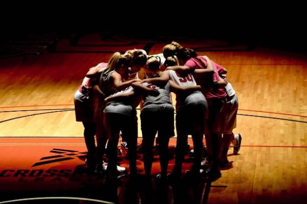 The Grace Women's Basketball team huddles for prayer before a game